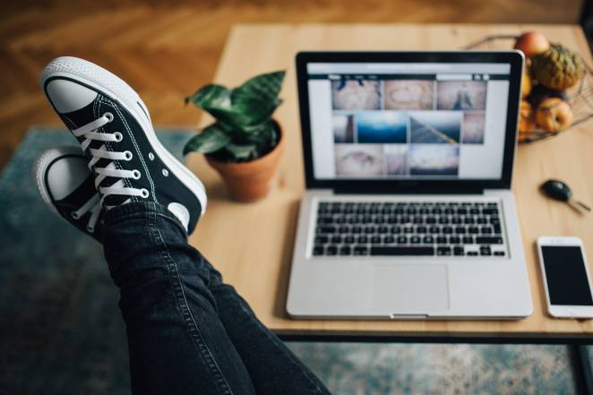 kaboompics_Woman in ripped jeans and black sneakers with a silver laptop on a wooden table.jpg