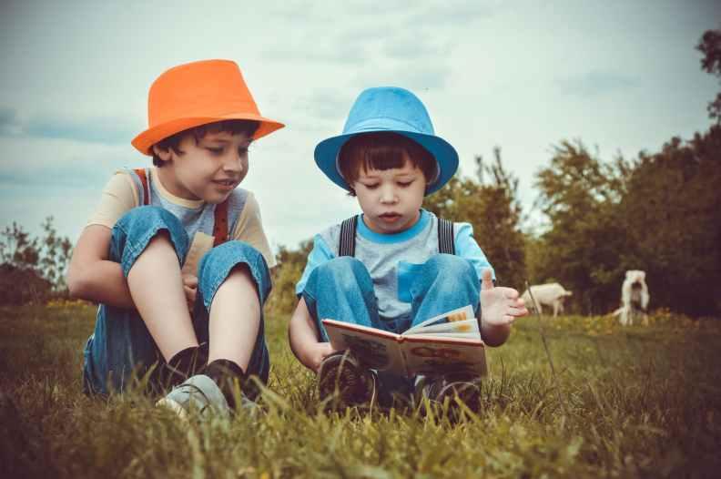kids sitting on green grass field